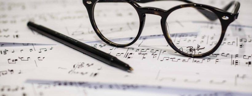 black framed panto-style eyeglasses beside black ballpoint pen. Photo by Dayne Topkin on Unsplash