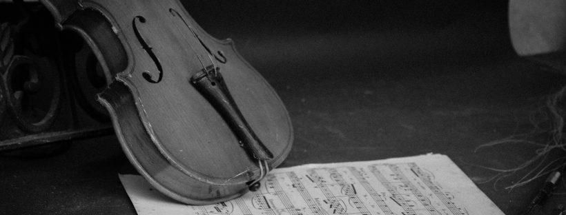 grayscale photography of violin on table with music sheet. Photo by Cameron Mourot on Unsplash